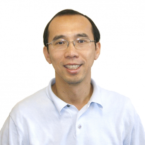A headshot of Raymond Ng smiling. He is wearing glasses and a white shirt.