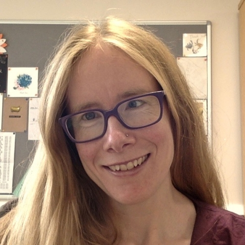 A headshot of Jenny Thomson smiling. Dr Thomson is wearing glasses and has long hair.