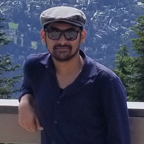 A picture of Venkata Praneeth Srungarapu wearing sunglasses and a hat, standing against a wooden fence with a view over Vancouver harbour in the background.