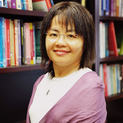 A headshot of Virginia Yip standing in front of bookshelves